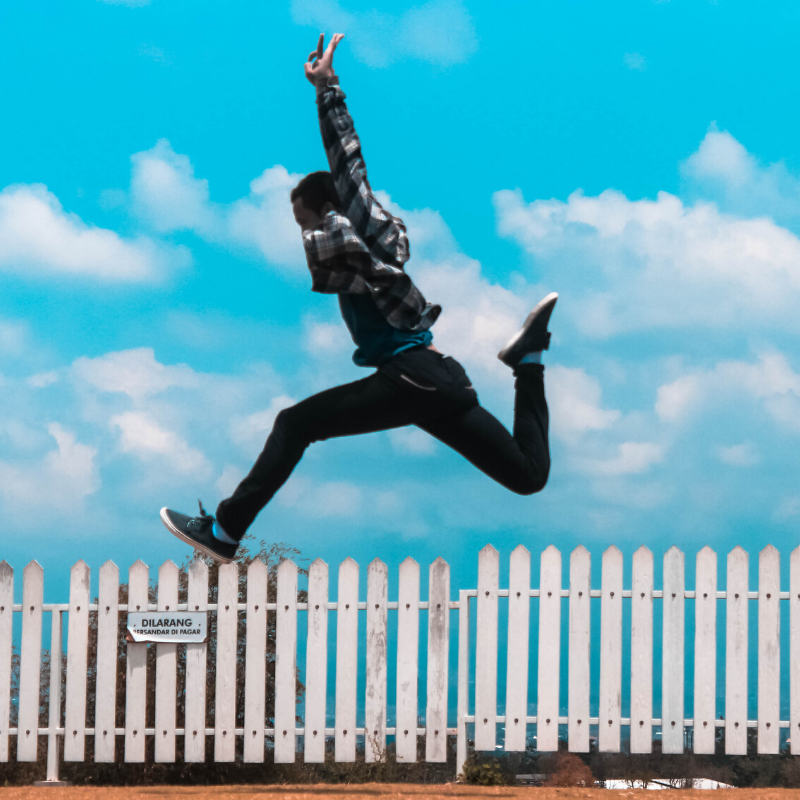 man excitedly jumping over fence