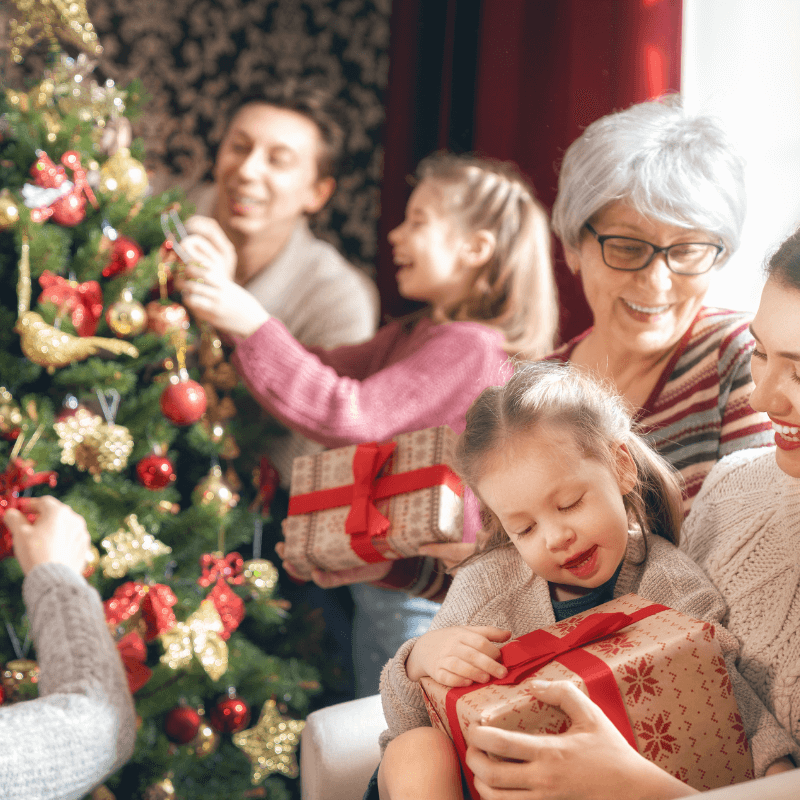 Multigenerational family around Christmas Tree
