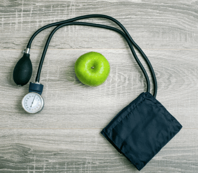 blood pressure cuff and a green apple on wood table
