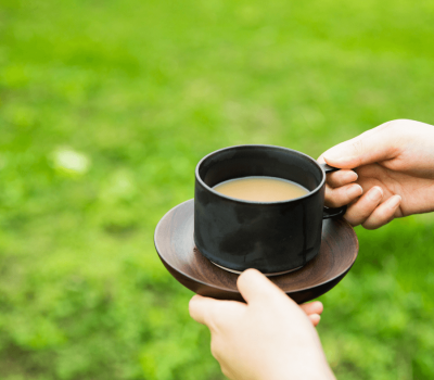 hands holding coffee cup with grass background - No Time for Self-care